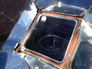After sieving out the simmered fruit, the liquid is being concentrated in a solar oven with oven cover slightly open to release moisture (MABurgess photo)