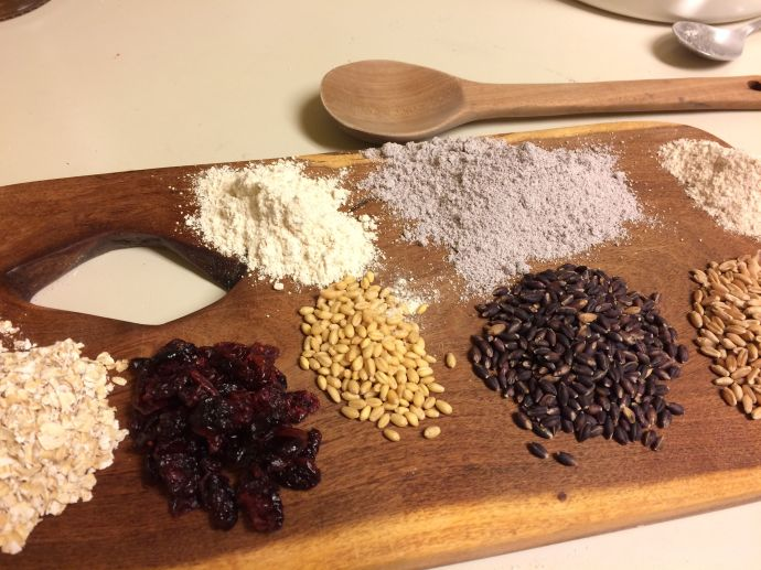 Ingredients for baking Valentine cookies--L to R rolled oats, dry cranberries, White Sonora wheat-berries and flour, Purple Prairie grain and lavender flour, local hard red wheat kernels and flour