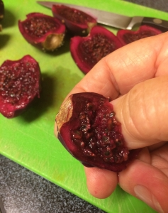 Scooping out seeds from prickly pear fruit cut in half
