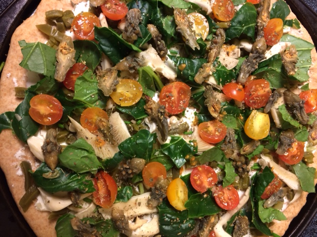 Totally local veggie pizza with cholla buds, nopalitos, acelgas, mushrooms, goat cheese and home-grown cherry tomatoes--ready to bake